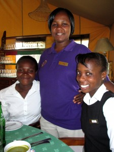 Carol and Mercy pose with a co-worker during their hospitality internship with Serena Hotels at Sweetwaters Tented Camp during the Transition Program